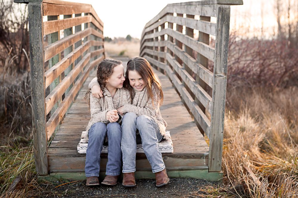 sisters whispering on rustic bridge - ellensburg children photographer