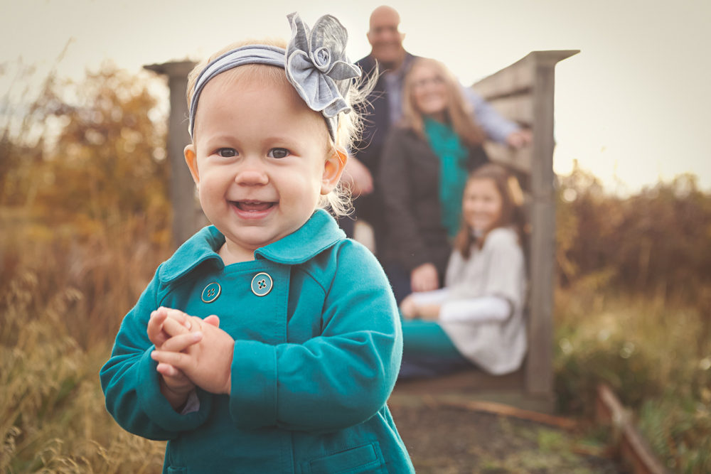 Lifestyle Fall Family Session Photo with family looking at adorable toddler
