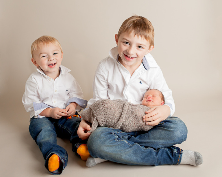 Nora Newborn session photo of big brothers and baby