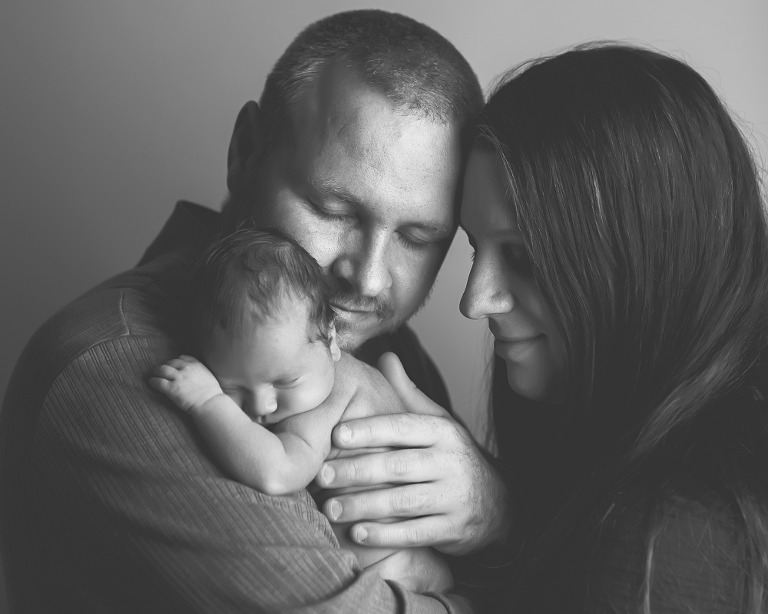 Nora Newborn session photo of baby cuddling with parents in black and white