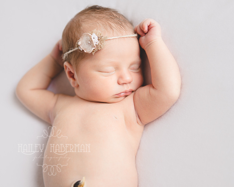 Nora Newborn session photo of baby asleep on back with hand above her head