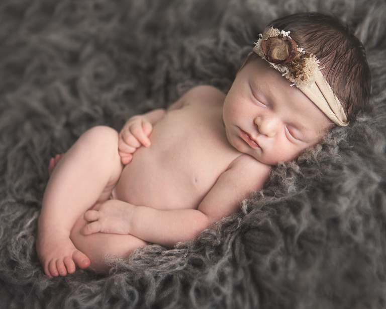 Ellensburg Newborn Photographer captures Baby Girl Kendall asleep on back in natural pose