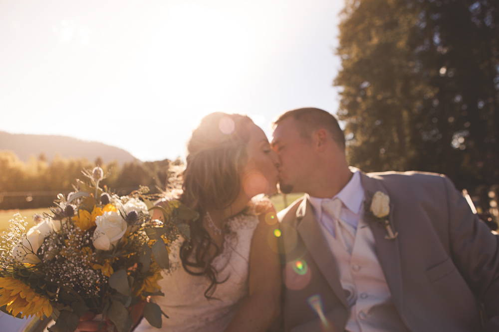 bride and groom kissing with sunflare - ritter farms cle elum wedding photographer