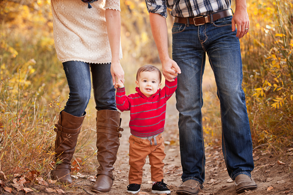 Lifestyle Fall Family Session Photo with parents holding child's hands